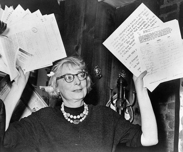 Jane Jacobs holding up planning documents