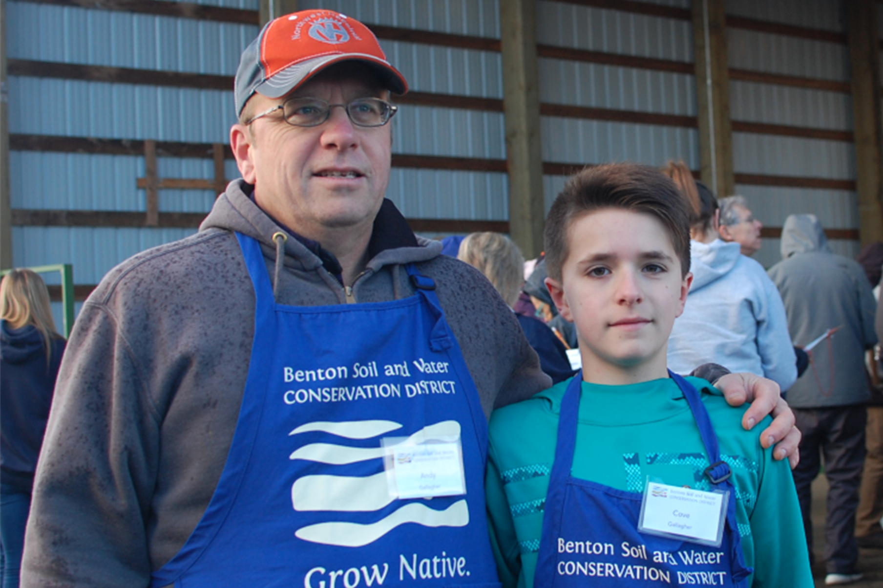 Andy Gallagher and his son sport blue Grow Native Aprons while volunteering at the Native Plant Sale