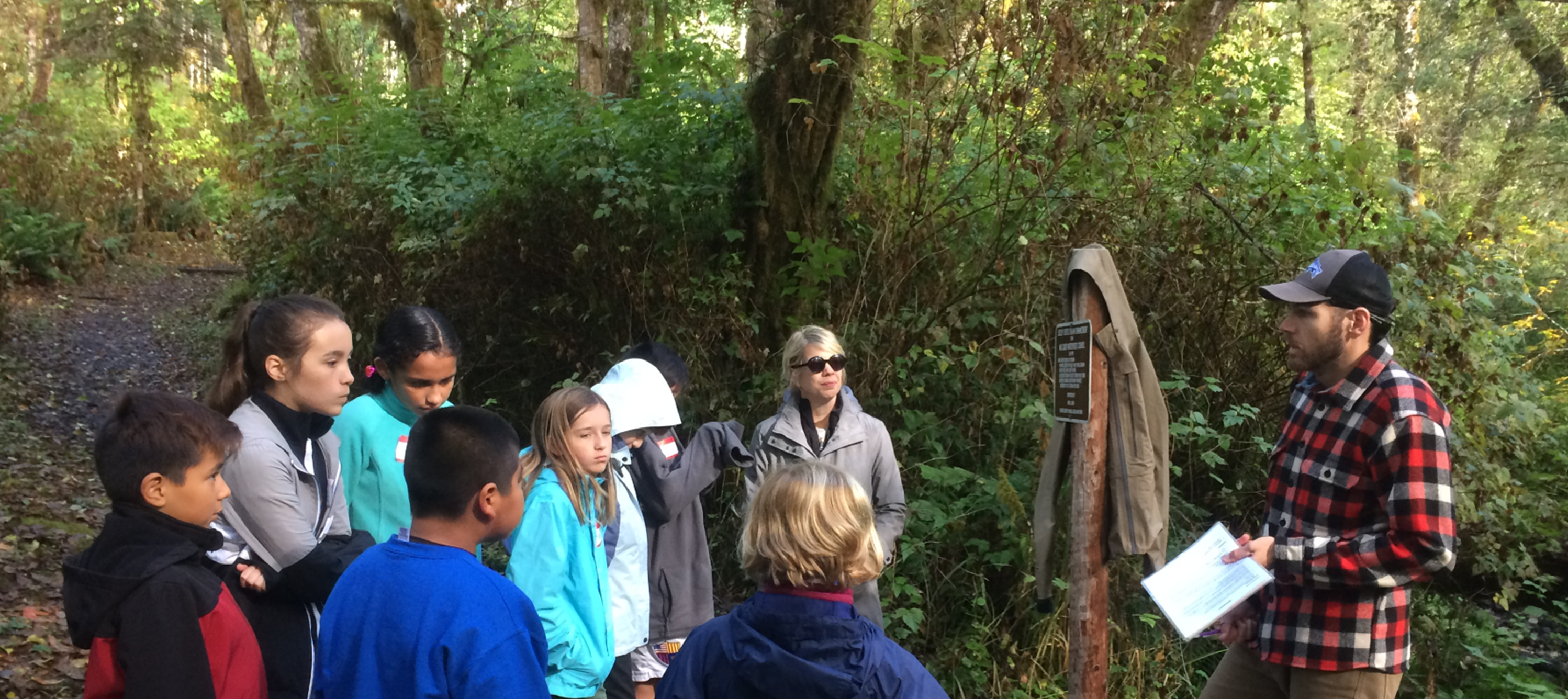 Karrie, at center with sunglasses, models active listening for her students on a Salmon Watch field trip.