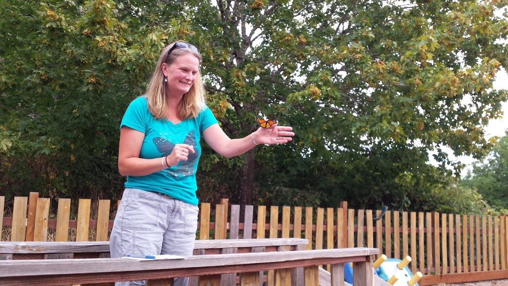 Momlly wearing a blue butterfly tshirt, releasing a monarch butterfly at a preschool event.