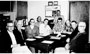 10 white men sitting at table with papers in front of them.