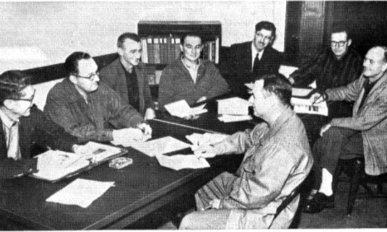 Eight men at a table signing papers.