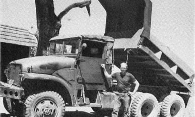 A man standing in front of a dump truck with raised bed.