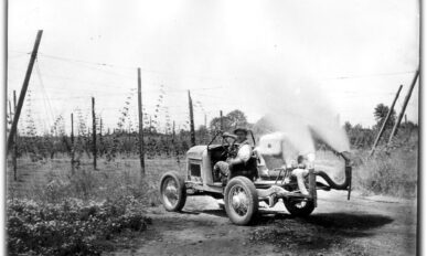 an early gas-powered tractor with two pipes extending from the bag with smoke billowing out of them.
