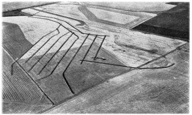 aerial view of farm field with eight parallel trenches dug into field.