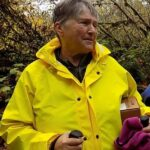 Pam Wilson at Clemens Park Salmon Watch field trip with yellow rain coat and hiking poles.